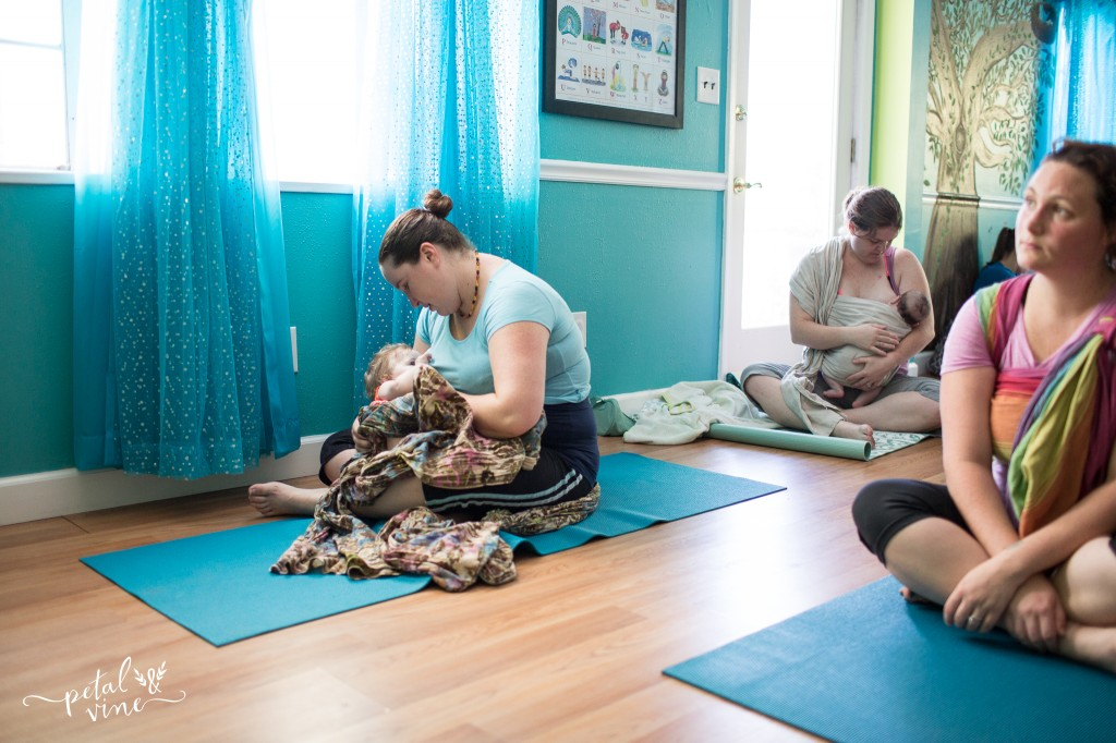 Two babies take a nursing break at a babywearing yoga class.