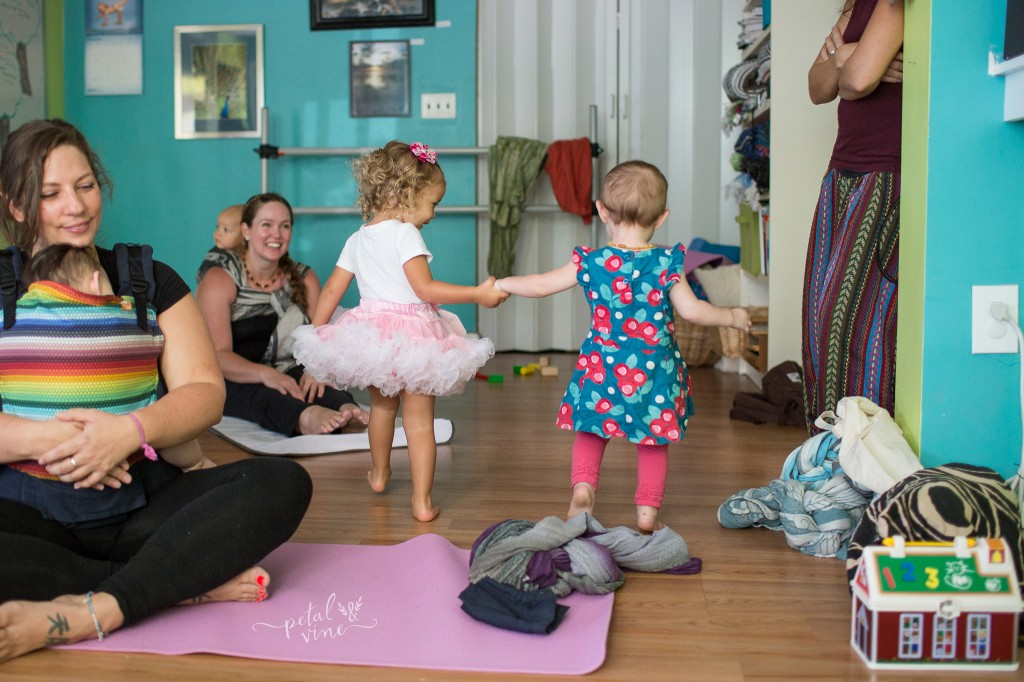 Toddlers holding hands at a yoga class.