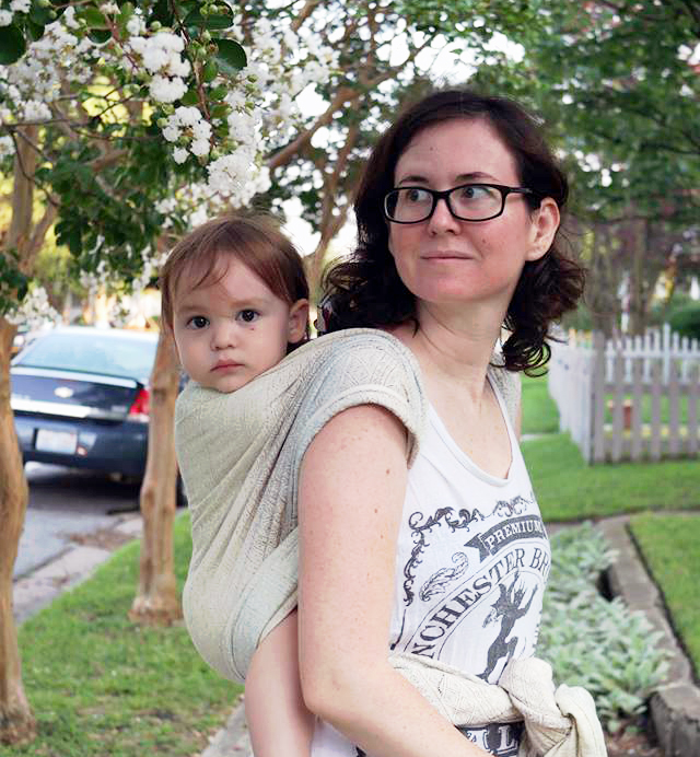Toddler wrapped on mom's back.