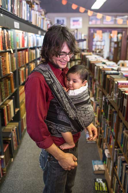 Dad with baby wrapped up in small, independent bookstore